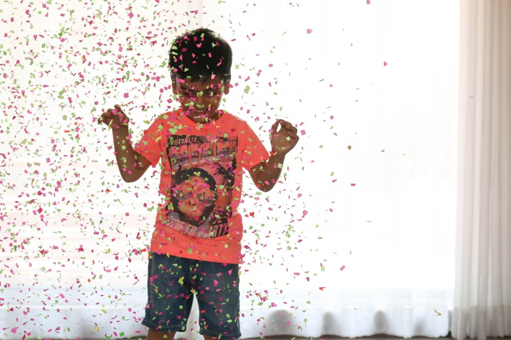 little boy jumping in confetti snow