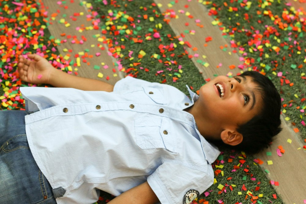 little boy playing in confetti