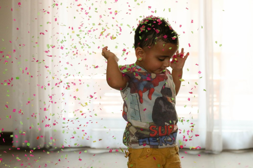 baby playing with confetti